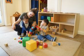 Lauren and kids playing with stacked coloured blocks